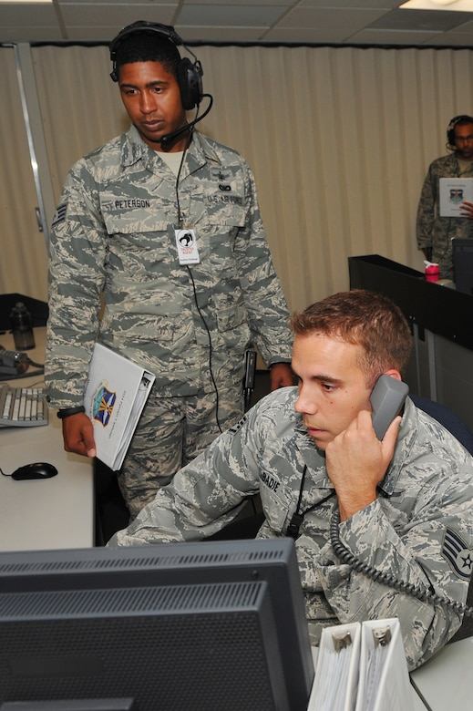 Staff Sgt. Glenn Labadie, 2nd Space Warning Squadron space operator, right, is evaluated by Staff Sgt. Harrel Peterson, 460th Operations Group, during the 460th Operations Group Panther Challenge Aug. 11, 2014, on Buckley Air Force Base, Colo. The challenge, held Aug. 4-13, was developed to provide members of Team Buckley an opportunity to improve their skills and expand their job knowledge in a competitive setting. Participants in the challenge included the 2nd and 8th Space Warning Squadrons, 460th Security Forces Squadron, and 460th Medical Group. (U.S. Air Force photo by Senior Airman Phillip Houk/Released)