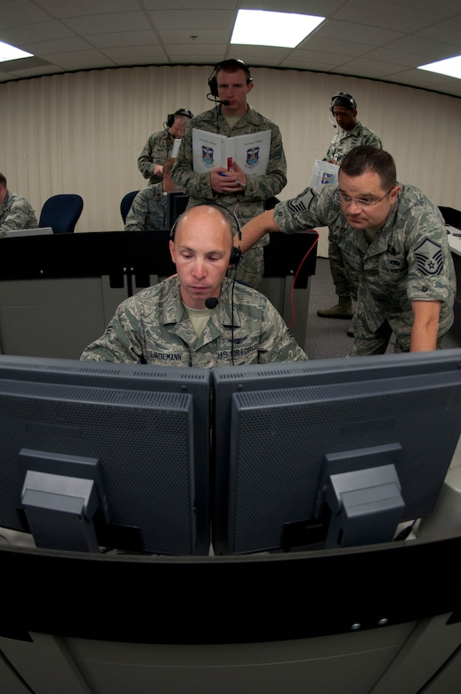Senior Airman Jeremy Lindemann, 8th Space Warning Squadron, seated, and Master Sgt. Michael Taylor, right, respond to a simulated event while being evaluated by members of the 460th Operations Support Squadron during the 460th Operations Group Panther Challenge Aug. 4, 2014, on Buckley Air Force Base, Colo. The challenge, held Aug. 4-13, was developed to provide members of Team Buckley an opportunity to improve their skills and expand their job knowledge in a competitive setting. Participants in the challenge included the 2nd and 8th Space Warning Squadrons, 460th Security Forces Squadron, and 460th Medical Group. (U.S. Air Force photo by Tech. Sgt. Kali L. Gradishar/Released)