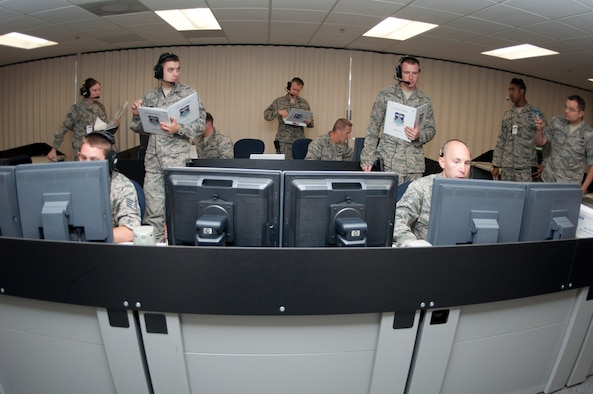 Members of the 8th Space Warning Squadron respond to simulated events while being evaluated by members of the 460th Operations Support Squadron during the 460th Operations Group Panther Challenge Aug. 4, 2014, on Buckley Air Force Base, Colo. The challenge, held Aug. 4-13, was developed to provide members of Team Buckley an opportunity to improve their skills and expand their job knowledge in a competitive setting. Participants in the challenge included the 2nd and 8th Space Warning Squadrons, 460th Security Forces Squadron, and 460th Medical Group. (U.S. Air Force photo by Tech. Sgt. Kali L. Gradishar/Released)