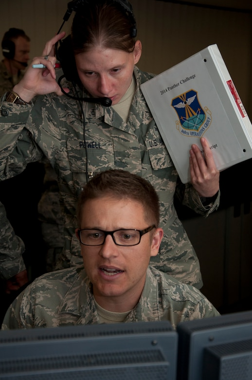 Tech. Sgt. Andrew Livingston, 8th Space Warning Squadron, seated, responds to a simulated event while Senior Airman Amber Powell, 460th Operations Support Squadron, evaluates his actions during the 460th Operations Group Panther Challenge Aug. 4, 2014, on Buckley Air Force Base, Colo. The challenge, held Aug. 4-13, was developed to provide members of Team Buckley an opportunity to improve their skills and expand their job knowledge in a competitive setting. Participants in the challenge included the 2nd and 8th Space Warning Squadrons, 460th Security Forces Squadron, and 460th Medical Group. (U.S. Air Force photo by Tech. Sgt. Kali L. Gradishar/Released)