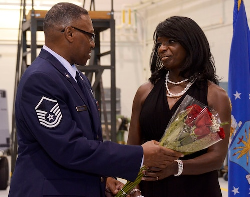 """Master Sgt. Charles McKenzie, 94th Maintenance Squadron electro environmental technician, presents a bouquet of roses to his wife, Carolyn, during his retirement ceremony Aug. 3 at Dobbins Air Reserve Base, Ga. """"It's people like Charles McKenzie that make my job fun,"""" said Lt. Col. Kerri Ebrecht, 94th Maintenance Squadron commander. """"He's here to support our mission, and he always puts forth the effort."""" (U.S.Air Force photo/Don Peek)"""