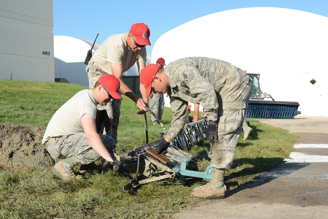 Airmen from the 210th Red Horse Squadron out of Kirtland Air Force Base, New Mexico, clean their equipment following a concrete project at the 115th Fighter Wing in Madison, Wis., Aug. 14, 2014. The group temporarily deployed to the 115 FW to complete various infrastructure projects on the base, while gaining real-world experience. (Air National Guard photo by Senior Airman Andrea F. Liechti)
