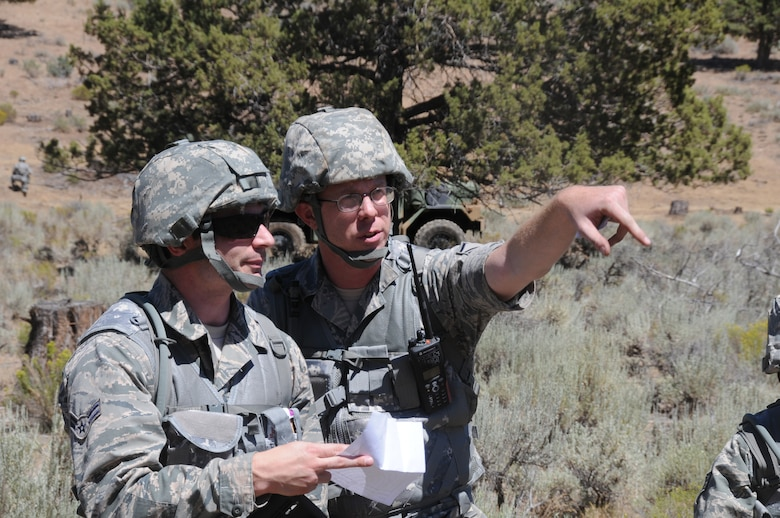 U.S. Air Force Master Sgt. Michael Moore directs Airman 1st Class Garrett Leanders, both of 270th Air Traffic Control Squadron,  on how to form up a perimeter during an area defense exercise July 24, near Bonanza, Oregon. The 270th ATCS controls the airspace for Kingsley Field but also has an expeditionary tasking; this year's annual training emphasized that capability and involved several exercises off base. (U.S. Air National Guard photo by Tech. Sgt. Jefferson Thompson/Released)