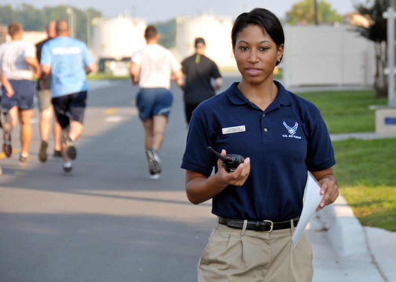U.S. Air Force Airman 1st Class Ishimine Johnson announces the beginning of the running portion for a physical training (PT) test over a radio to fellow PT leaders at the 125th Fighter Wing, Jacksonville International Airport, Jacksonville Florida., Aug. 17, 2014. Johnson spends her time off from the Air National Guard training for and competing in bodybuilding competitions. (U.S. Air Force photo by Staff Sgt. Troy Anderson/RELEASED)