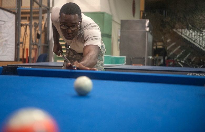 Senior Airman Martini Frazier, 51st Civil Engineer Squadron heating, ventilation, air condition and refrigeration journeyman, shoots a game of pool at Osan AB, Republic of Korea, Aug. 20, 2014. During lunch breaks, members of the shop would play pool or ping pong. (U.S. Air Force photo by Senior Airman Matthew Lancaster)
