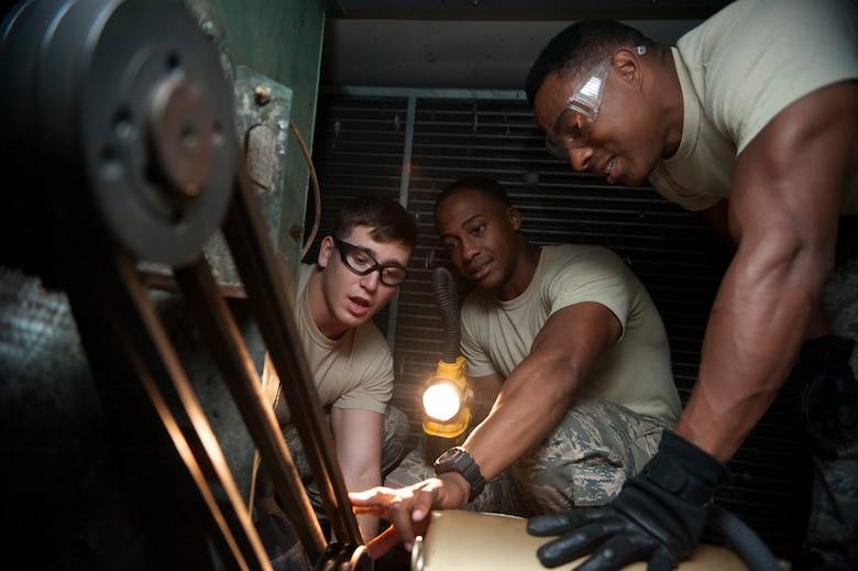Airman 1st Class Todd Gonsalves,51st Civil Engineer Squadron heating, ventilation, air condition and refrigeration apprentice, Senior Airman Steven Williams and Senior Airman Chaz Wilson, 51st CES HVAC-R journeymen, check the leveling on a motor belt at Osan AB, Republic of Korea, Aug. 20, 2014. HVAC shop members would go out with two or more people to accomplish each work order. (U.S. Air Force photo by Senior Airman Matthew Lancaster)
