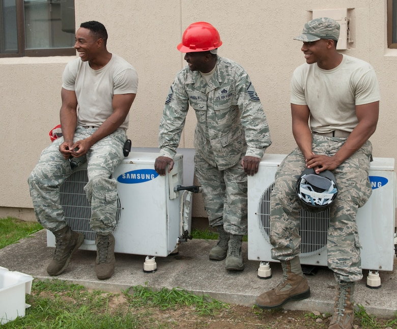 Senior Airman Chaz Wilson, Senior Airman Steven William, 51st Civil Engineer Squadron heating, ventilation, air condition and refrigeration journeymen, and Master Sgt. Octavius Smalls, 51st CES NCO in charge of HVAC-R, share a laugh at Osan AB, Republic of Korea, Aug. 14, 2014. During breaks, members of the shop tell jokes to pass the time. (U.S. Air Force photo by Senior Airman Matthew Lancaster)