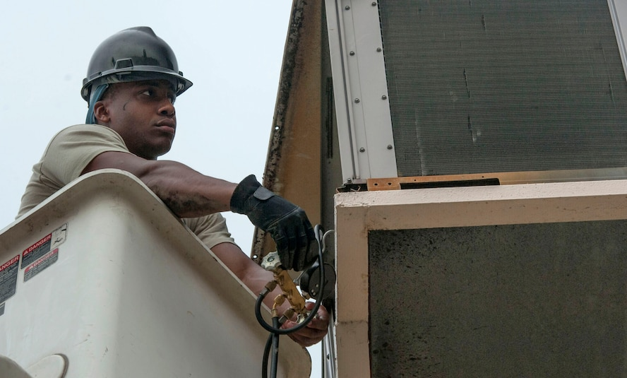 Senior Airman Steven Williams, 51st Civil Engineer Squadron heating, ventilation, air condition and refrigeration journeyman, performs maintenance on an AC unit at Osan AB, Republic of Korea, Aug. 14, 2014. The HVAC shop is in charge of making sure all the AC units on base are working properly. (U.S. Air Force photo by Senior Airman Matthew Lancaster)