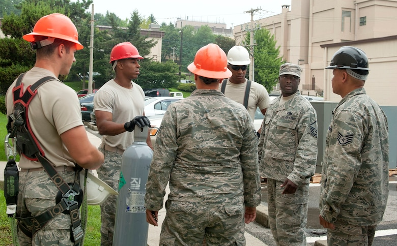 Members of the 51st Civil Engineer Squadron heating, ventilation, air condition and refrigeration shop have a group discussion before a job at Osan AB, Republic of Korea, Aug. 14, 2014. During these discussions, details about the task are clearified and properly assigned. (U.S. Air Force photo by Senior Airman Matthew Lancaster)