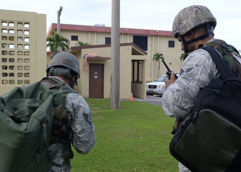 Staff Sgt. Jomer Bautista, 36th Comptroller Squadron customer service technician, and Senior Airman Tom Hammonds IV, 36th Contracting Squadron contract specialist, identify a simulated casualty while performing a post-attack reconnaissance sweep during Exercise Beverly Palm 14-04 Aug. 20, 2014, on Andersen Air Force Base, Guam. The 12-hour exercise took place to enhance the skills of Airmen in preparation for real-world contingencies. (U.S. Air Force photo by Airman 1st Class Amanda Morris/Released)