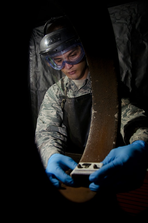 Airman 1st Class Ashton Surber, 36th Maintenance Squadron non-destructive inspection journeyman, uses a magnetic particle machine to search for defects during an aircraft part inspection  Aug. 21, 2014, on Andersen Air Force Base, Guam. NDI Airmen provide support to the structural maintenance program, which ensures air and space equipment are safe, serviceable and in mission-ready condition. (U.S. Air Force photo by Senior Airman Katrina M. Brisbin/Released)