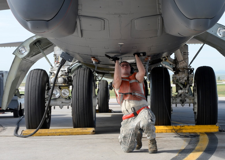 Airman 1st Class Eriberto Gonzalez Gomez secures flaps underneath a B-52 Stratofortress during launch procedures as part of a standoff weapons integration training exercise Aug. 14, 2014, on the flightline at Ellsworth Air Force Base, S.D. Gonzalez Gomez, a 5th Aircraft Maintenance Squadron crew chief from Minot Air Force Base, N.D., is responsible for maintaining and supervising the more than 40-year-old aircraft that can carry up to 70,000 pounds of munitions and is capable of flying at high subsonic speeds at altitudes up to 50,000 feet. (U.S. Air Force photo/Senior Airman Anania Tekurio)