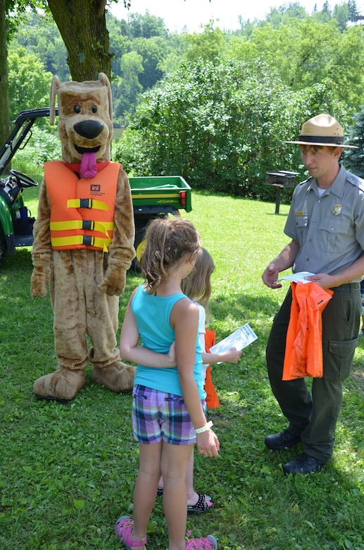 Bobber the water safety dog and park ranger Brad Labadie talk water safety with children at Eau Galle Recreation Site in Spring Valley, Wis., July 11, 2014.