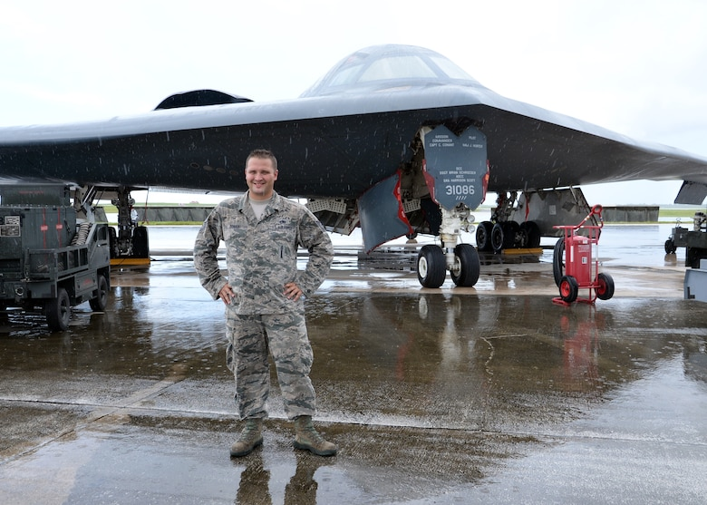 U.S. Air Force Tech Sgt. Brock Schuld, 131st Aircraft Maintenance Squadron maintainer, poses in front of a B-2 Spirit bomber during a deployment, Andersen Air Force Base, Guam, Aug. 22, 2014.  The bombers and approximately 200 support Airmen, assigned to the 509th Bomb Wing at Whiteman Air Force Base, Mo., deployed to Guam Aug. 6, 2014 to improve combat readiness and ensure regional stability.  Bomber deployments help maintain stability in the region while allowing units to become familiar with operating in the theater according to USPACOM.  (U.S. Air Force photo by Senior Airman Cierra Presentado/Released)