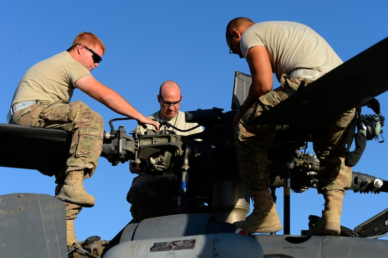 U.S. Air Force Senior Airman Benjamin Martin, Tech. Sgt. Korey Ehinger, and Senior Airman LeSean Young-Dilworth, 455th Expeditionary Aircraft Maintenance Squadron, perform a preflight inspection on a HH-60G Pave Hawk at Bagram Air Field, Afghanistan, July 19, 2014. Martin is a Colorado Springs, Colo. native, Ehinger is a Ft. Wayne, Ind. native, and Young-Dilworth is a Pembroke Pines, Fla. native. All are deployed from the 923rd Aircraft Maintenance Squadron, Davis-Monthan Air Force Base, Ariz. (U.S. Air Force photo by Senior Airman Sandra Welch)