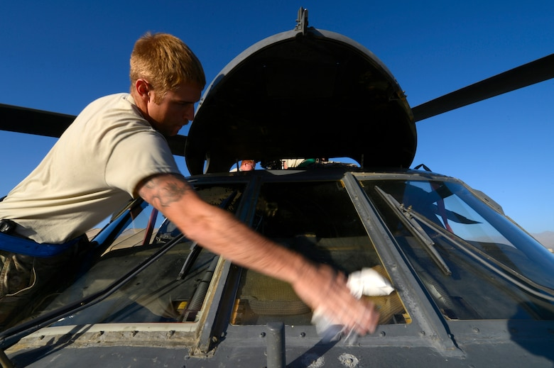 U.S. Air Force Senior Airman Doug Spencer, 455th Expeditionary Aircraft Maintenance Squadron electrical technician, washes the windows of a HH-60G Pave Hawk during a preflight inspection at Bagram Air Field, Afghanistan, July 19, 2014. Spencer is a Plymouth, Ind., native deployed from the 923rd Aircraft Maintenance Squadron, Davis-Monthan Air Force Base, Ariz. (U.S. Air Force photo by Senior Airman Sandra Welch)