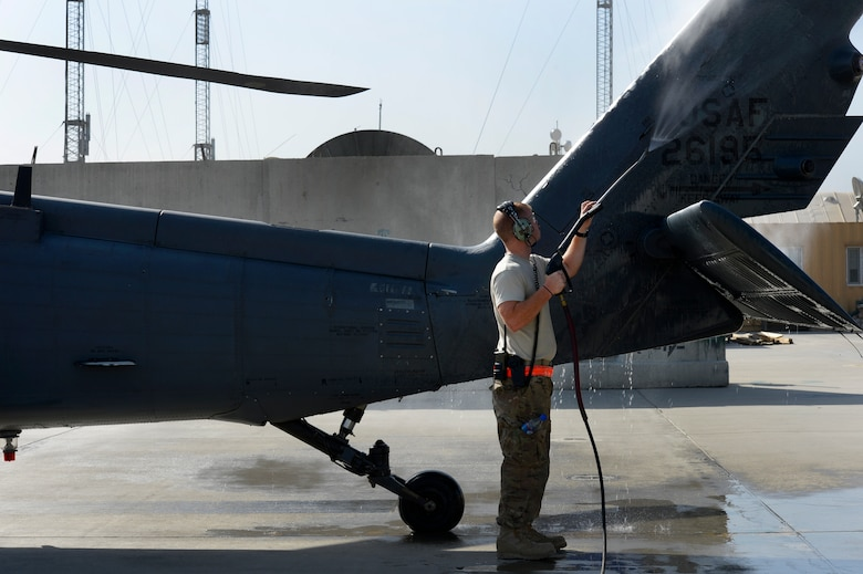 Staff Sgt. James Henderson, 455th Expeditionary Aircraft Maintenance Squadron weapons technician, washes a HH-60G Pave Hawk helicopter during a preflight inspection at Bagram Air Field, Afghanistan, July 10, 2014. Henderson, an Oklahoma City, Oklahoma native, is deployed from the 923rd Aircraft Maintenance Squadron, Davis-Monthan Air Force Base, Arizona. (U.S. Air Force photo by Senior Airman Sandra Welch/Released)
