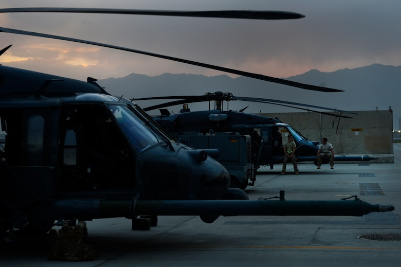 Senior Airman Lucas Brogdon, 455th Expeditionary Aircraft Maintenance Squadron crew chief, and Senior Airman Cody Ficsher, 455th EAMXS communication and navigation specialist, wait for an HH-60G Pave Hawk helicopter to take-off from Bagram Air Field, Afghanistan, July 9, 2014. Brogdon, a Lexington, North Carolina native, and Ficsher, a Visalia, California native, are deployed from the 923rd Aircraft Maintenance Squadron, Davis-Monthan Air Force Base, Arizona. (U.S. Air Force photo by Senior Airman Sandra Welch/Released)