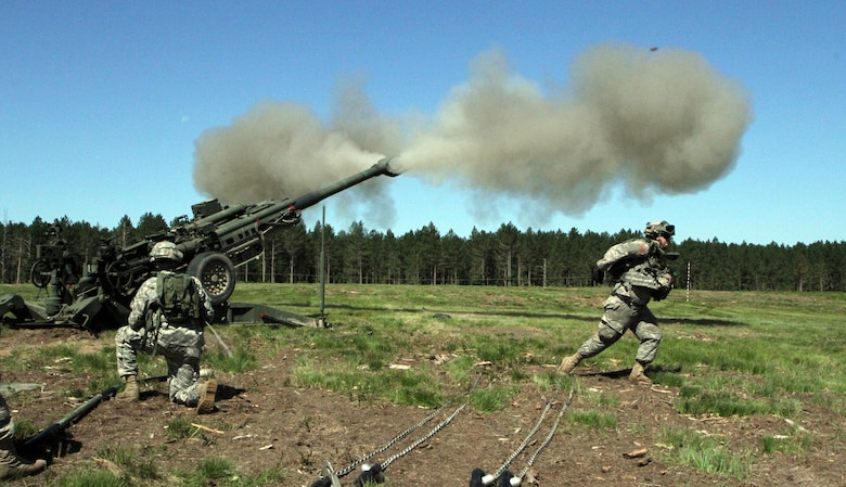 Soldiers assigned to gun two, Bravo Battery, 1st Battalion, 119th Artillery Regiment, Michigan National Guard, fire the M777A1 howitzer during the eXportable Combat Training Capability Exercise held at the Camp Grayling Joint Maneuver Training Center, Mich., July 18, 2014. (U.S. Army photo by Sgt. Jeremy Miller/Released)