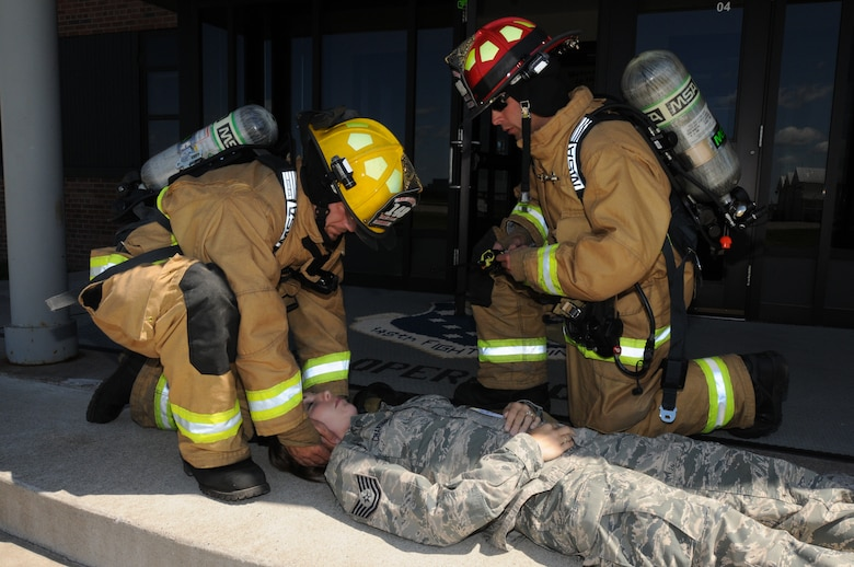 Two firefighters, from the  148th Fighter Wing, Minnesota Air National Guard, treat a simulated casualty for wounds Aug. 12, 2014 during a recent natural disaster preparedness response exercise in Duluth, Minn.  The Wing, along with other Minnesota National Guard units and civilian agencies jointly participated in the state-wide Vigilant Vortex exercise.  (U.S. Air National Guard photo by Tech. Sgt. Brett R. Ewald/Released)
