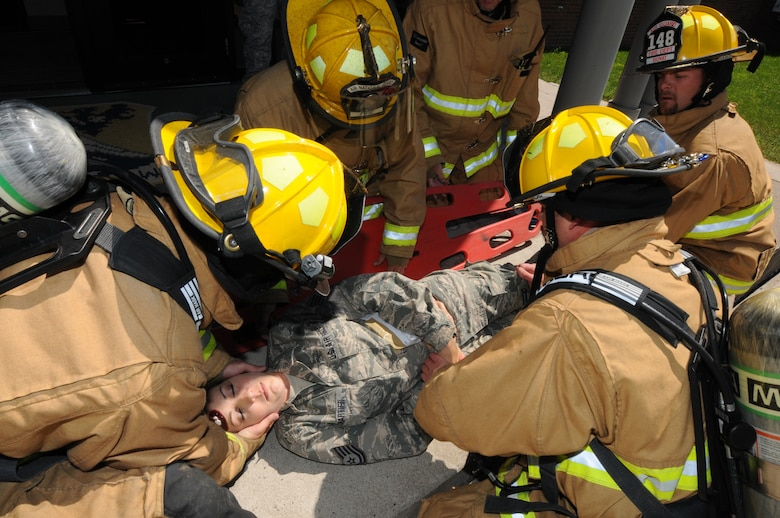 Firefighters from the 148th Fighter Wing, Minnesota Air National Guard, prepare to move a simulated casualty onto a backboard for evacuation Aug. 12, 2014 during a recent natural disaster preparedness response exercise in Duluth, Minn.  The Wing, along with other Minnesota National Guard units and civilian agencies jointly participated in the state-wide Vigilant Vortex exercise.  (U.S. Air National Guard photo by Tech. Sgt. Brett R. Ewald/Released)