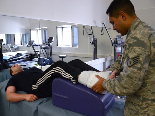 Staff Sgt. Mario Jimenez, 86th Medical Operations Squadron Physical Therapy technician, applies an ice pack to the ankle of Senior Airman James Harrod, 693rd Intelligence, Surveillance and Reconnaissance Group operations training manager, at the end of a physical therapy session at Ramstein Air Base, Germany, Aug. 19, 2014. Without formal treatment and physical therapy, service members run the risk of re-injuring themselves and causing greater damage to an area. (U.S. Air Force photo/Senior Airman Timothy Moore)