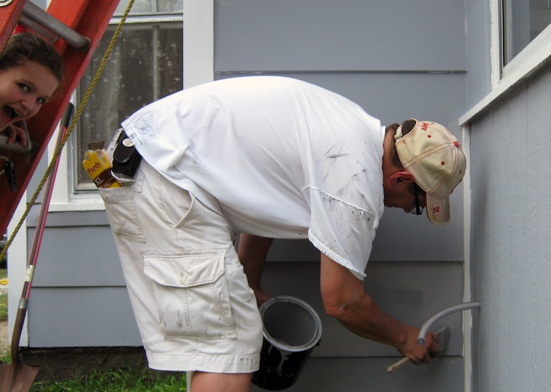 John Bertino, Engineering Division Chief at Omaha District does some last minute paint touch ups during the 2014 Paint-A-Thon, while his daughter Jill peeks through the steps of one of the many ladders used during the painting of the home in Council Bluffs, Iowa.
