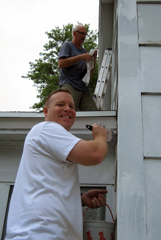 Jim Pakiz, Assistant District Counsel and a member of the 2014 Omaha District Leadership Development Class, paints the lower section of the house, while John Remus, Hydrologic Engineering Branch Chief, gets the higher portions of the Paint-A-Thon house.