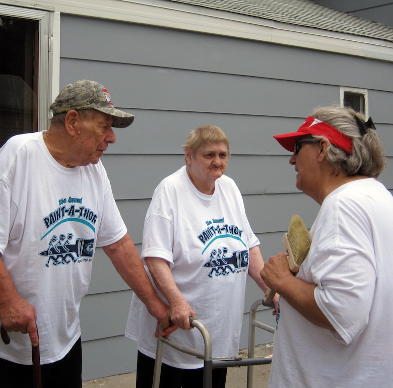 Joyce Ridout, Brush Up Nebraska Paint-A-Thon team leader, reveals the completed home to its homeowners in Council Bluffs, Iowa, Erich and Arlene Schwartz.