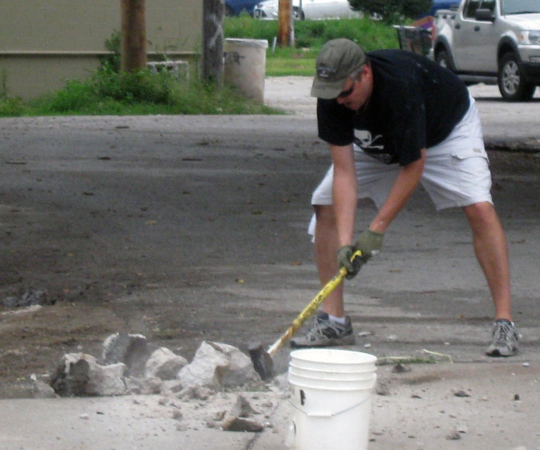 Tom O'Hara, III, Omaha District Executive Officer, breaks down the old cement porch step into smaller pieces with the force of a sledgehammer.