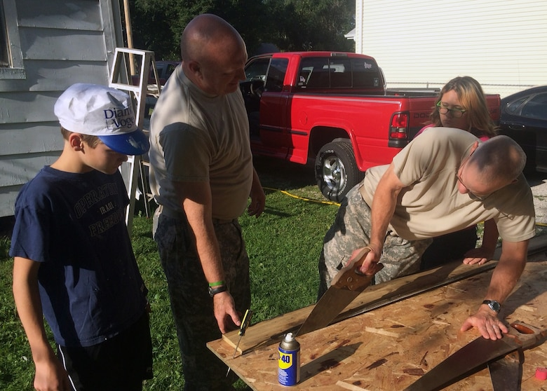 Col Joel Cross, Omaha District Commander saws the plywood used to replace the old cellar door of the home being painted for Paint-A-Thon 2014, while Lt Col Michael Sexton, Deputy Commander, oversees the process. Meanwhile Brian Cross and a teenage neighbor girl look on.