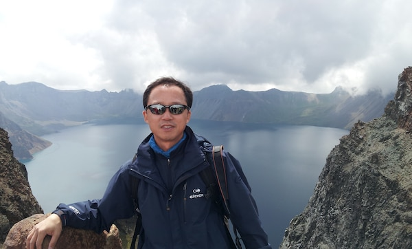 Dr. Pak Chun-pom, chief of the district's data management section, poses for a picture in front of Heaven Lake, in the caldera atop Mount Baekdu. Mount Baekdu is an active volcano on the border of North Korea and China.