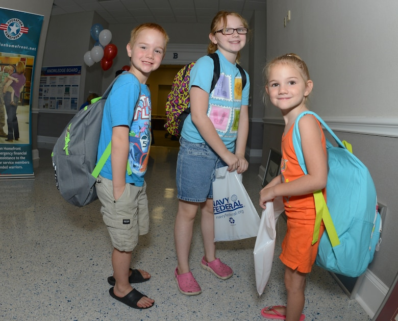 Military Children from grades k-12 walk away with pack packs almost too heavy for them to carry with big smiles on their faces during the Operation Homefront Back Pack Brigade giveaway held at the 136th Airlift Wing, Naval Air Station Fort Worth Joint Reserve Base, Texas, Aug. 15, 2014. This annual event provides free school supplies to the children. (Air National Guard photo by Senior Master Sgt. Elizabeth Gilbert/released)