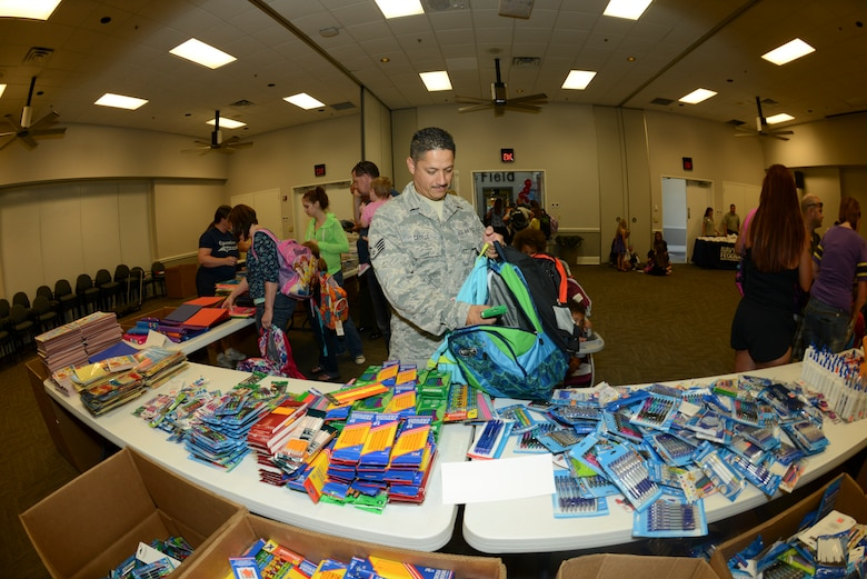 U.S. Air Force Staff Sgt. Jose Cedillo, 136th Communications Flight, Texas Air National Guard, browses through the many school-supply items to fill his children's pack backs during the Operation Homefront Back Pack Brigade giveaway held at Naval Air Station Fort Worth Joint Reserve Base, Texas, Aug. 15, 2014. Military members E-6 and below with school-age children from grades k-12 receive back packs from this annual event. (Air National Guard photo by Senior Master Sgt. Elizabeth Gilbert/released)