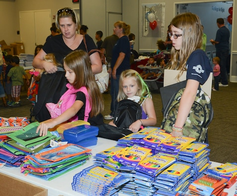 Military families of E-6 and below with school age children from K-12 browse through the many school-supply itmes with their brand new packpacks, filling them with up to 30 items at the 136th Airlift Wing, Naval Air Station Fort Worth Joint Reserve Base, Texas, Aug.15, 2014. Operation Homefront Back Pack Brigade partners with Dollar Tree and Office Depot poviding the free school supplies to military kids. (Air National Guard photo by Senior Master Sgt. Elizabeth Gilbert/released)