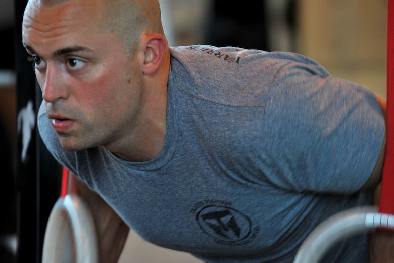 U.S. Army Sgt. Morgan Whitman, U.S. Africa Command all source analyst from Andover, Minn., performs a ring push-up during the Coe Hero workout of the day at RAF Molesworth, Aug. 14, 2014. The monthly Hero WOD was held to honor U.S. Army Sgt. Keith Adam Coe, who died April 27th, 2010 in Khalis, Iraq of wounds sustained from an explosive device set off by enemy forces. (U.S. Air Force photo by Staff Sgt. Ashley Hawkins/Released)