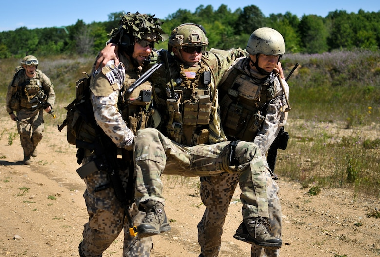 Latvian Capt. Armands Rutkis (left) and Cpl. Janis Gabranis (right), both tactical air control party specialists with the Latvian National Armed Forces, carry U.S. Air Force Senior Airman Lance A. Liggett to a medical evacuation point after a simulated roadside bomb explosion at Operation Northern Strike in Grayling Air Gunnery Range, Grayling, Mich., Aug. 14, 2014. Northern Strike was a 3-week-long exercise led by the National Guard that demonstrated the combined power of joint and multinational air and ground forces. TACPs with the Air National Guard's 169th ASOS from Peoria, Ill., and more than 5,000 other armed forces members from 12 states and two coalition nations participated in the combat training. (U.S. Air National Guard photo by Staff Sgt. Lealan Buehrer/Released)