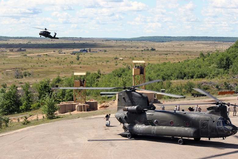 A UH-60 Black Hawk helicopter maneuvers into position after a CH-47 Chinook helicopter lands at the Grayling Air Gunnery Range during Operation Northern Strike, Aug. 13, 2014. Both aircraft are operated by the Michigan Army National Guard. Twenty-four units from 12 states and two coalition partners will participate in the three-week event. Operation Northern Strike will occur from Aug. 4 - 22, 2014, at the Alpena Combat Readiness Training Center and Camp Grayling Joint Maneuver Training Center. Over 300 Total Force fighter, bomber, mobility, and rotary sorties are planned in support of live fire exercises in order to meet stated objectives for participating units. (U.S. Air National Guard photo by Tech. Sgt. Dan Heaton)
