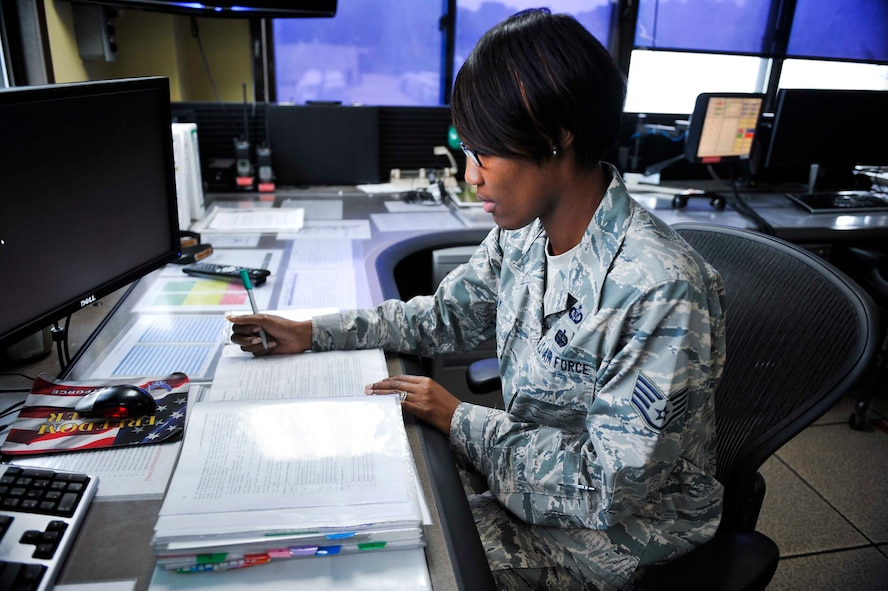 Staff Sgt. Jacquetta Ray, 731st Airlift Mobility Squadron senior command post controller and non-commissioned officer of reports, looks up a mission delay description on Osan Air Base, Republic of Korea, Aug. 21, 2014. Ray is this week's Airman Spotlight winner. (U.S. Air Force photo/Senior Airman David Owsianka)