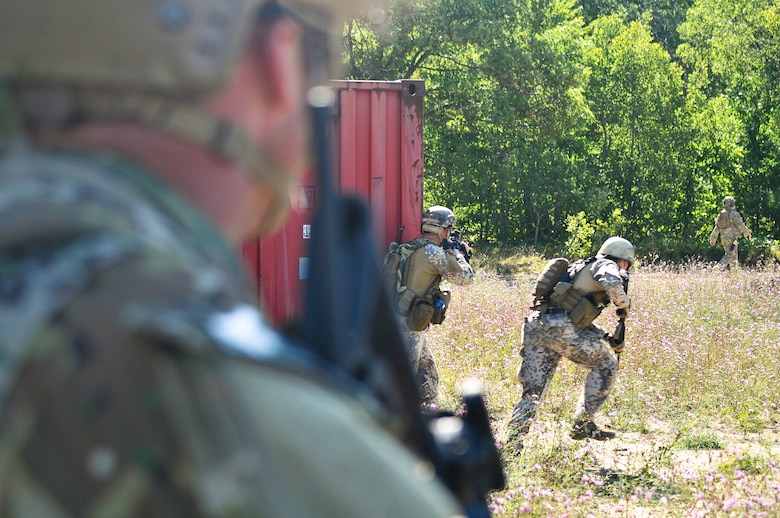 Tactical air control party specialists with the Latvian National Armed Forces advance on enemy forces while a TACP with the 169th Air Support Operations Squadron provides cover fire after an ambush during a reconnaissance mission at Operation Northern Strike in Grayling Air Gunnery Range, Grayling, Mich., Aug. 14, 2014. Northern Strike was a 3-week-long exercise led by the National Guard that demonstrated the combined power of joint and multinational air and ground forces. (U.S. Air National Guard photo by Staff Sgt. Lealan Buehrer)