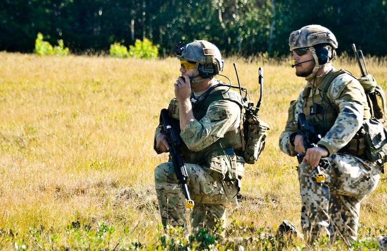 Master Sgt. John M. Oliver (left), Tactical Air Control Party specialist with the 169th Air Support Operations Squadron, and Latvian 1st Sgt. Modris Circenis, TACP with the Latvian National Armed Forces, communicate with a team flanking an enemy position during a reconnaissance mission at Operation Northern Strike in Grayling Air Gunnery Range, Grayling, Mich., Aug. 14, 2014.  (U.S. Air National Guard photo by Staff Sgt. Lealan Buehrer)