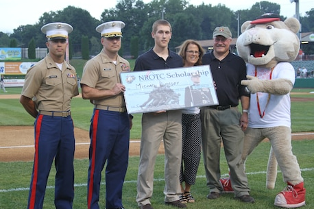 Michael Landry (center) was presented a check at the start of the Aug. 21, 2014 game between the Tri-City Valleycats and the Vermont Lake Monsters, for being awarded an NROTC scholarship from Recruiting Station Albany. Also on hand for the presentation were Capt. Luis Murillo (left), RS Albany executive officer, and Maj. Mastin M. Robeson Jr., RS Albany commanding officer, as well as Landry's parents and the Valleycats mascot.