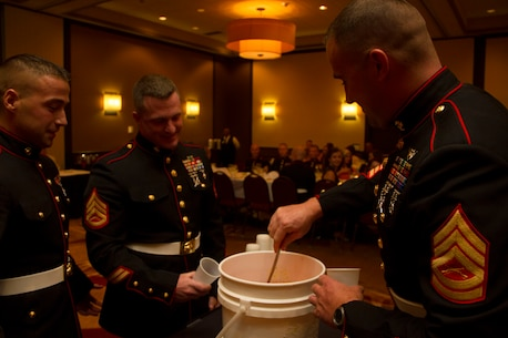 """Staff Sgt. Paul Miller III, SNCOIC of Recruiting Substation Fond du Lac, Staff Sgt. Peter Vargo, SNCOIC of Recruiting Substation Appleton, and Gunnery Sgt. Jeremy Simms, Operations Chief of Recruiting Station Milwaukee, (left to right) prepare to drink from the """"grog"""" during RS Milwaukee's first Dining Out, Aug. 20 in Brown Deer, Wis.  The """"grog"""" is a less than appetizing mix of mystery ingredients that Marines may have to drink from if they are caught violating the """"Rules of the Mess."""""""