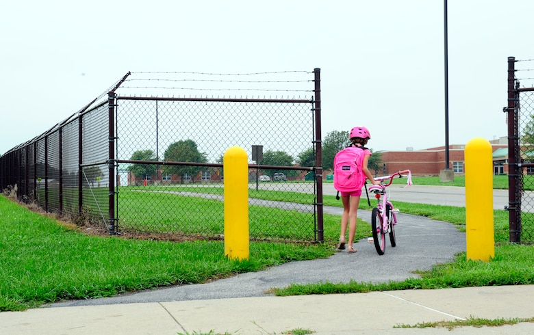 Children use the Patriots Landing housing pedestrian gate to ride their bikes to Scott Elementary School August 18, 2014. Individuals using the gate must walk through it. This requires children who ride bikes to stop and get off then walk ensuring safety because of the large amount of traffic.  (U.S. Air Force photo/Staff Sgt. Stephenie Wade)