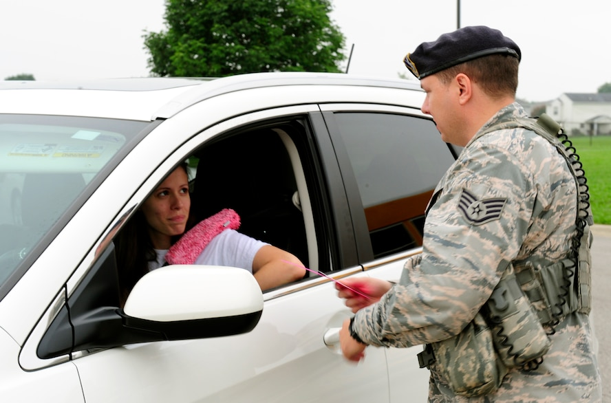 Staff Sgt. John Anderson, 375th Security Force Squadron, checks the identification of a parent prior to letting her back on Scott Air Force Base, Ill., after dropping her children off at school August 18, 2014. Drivers crossing from the elementary school to the base need to have their government ID card and a pink card from the school, giving them authorization to enter the base. (U.S. Air Force photo/Staff Sgt. Stephenie Wade)