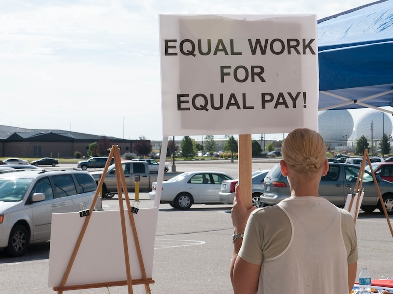 Tech. Sgt. Amy Szpak, Air Reserve Personnel Center retirement counselor, holds a sign during a peaceful protest in honor of Women's Equality Day Aug. 26, 2014, on Buckley Air Force Base, Colo. Women's Equality Day commemorates the ratification of the 19th Amendment, granting women the right to vote. Today, it is celebrated in honor of modern day women's rights to be seen as equals to men. (U.S. Air Force photo by Airman 1st Class Samantha Saulsbury/Released)