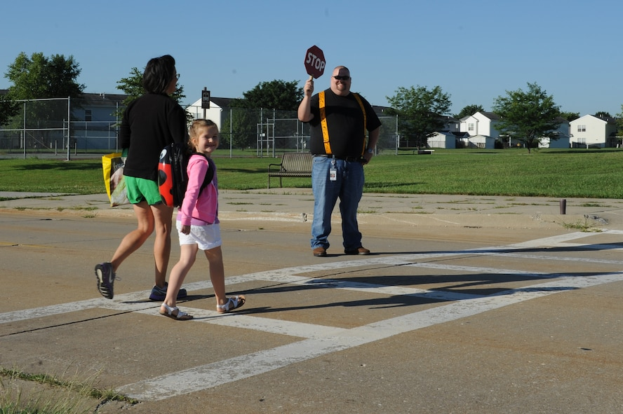 A student and her mother are greeted by a crossing guard at Scott Elementary School on the first day of school, August 13, 2014, at Scott Air Force Base, Ill. Crossing guards ensure students who cross from base housing or the youth center to Scott Elementary School are safe in the crosswalk, where the speed limit is 15 miles per hour. (U.S. Air Force photo by Senior Airman Sarah Hall-Kirchner/Released)