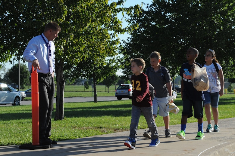 Fritz Holcomb, Scott Elementary School assistant principal, greets students as they depart the bus on the first day of school at Scott Air Force Base, Ill. on August 13, 2014. Students get to school in a variety of ways, such as walking, riding a bus, or being dropped off by car. (U.S. Air Force photo by Senior Airman Sarah Hall-Kirchner/Released)