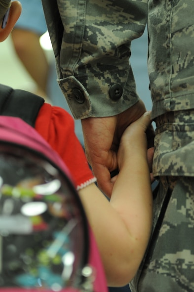 A military parent leads their child by the hand into Scott Elementary School on August 13, 2014 at Scott Air Force Base, Ill. for the first day of school. The school day begins at 8:15 a.m. at Scott Elementary School. (U.S. Air Force photo by Senior Airman Sarah Hall-Kirchner/Released)