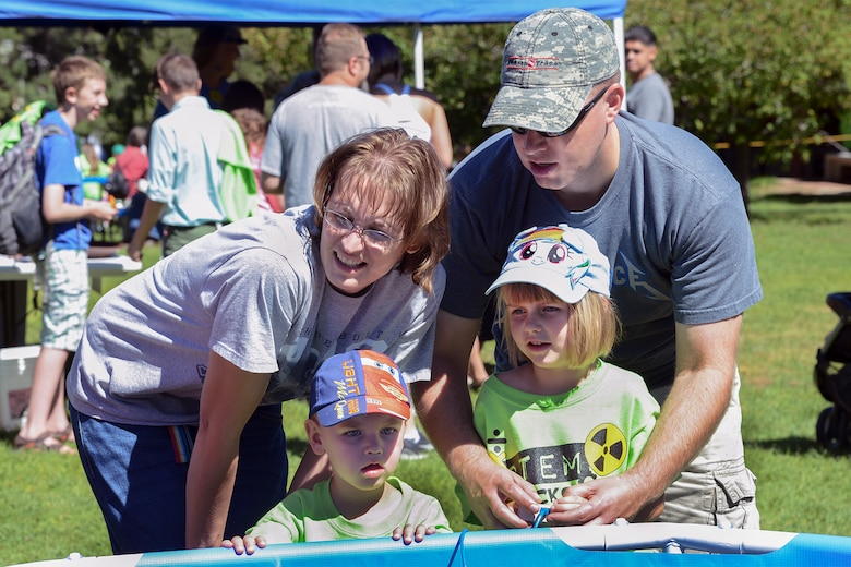 PETERSON AIR FORCE BASE, Colo. – Army Staff Sgt. J.D. Seamons and his wife Angie, help their children Hailey and Caleb control an underwater rover at STEM Rocks! at the Peterson Air and Space Museum Aug. 23. Children and parents could visit nearly 30 booths to learn about Science, Technology, Engineering and Math in a fun, carnival-like environment. (U.S. Air Force photo/Tech. Sgt. Jared Marquis)